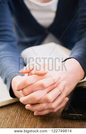 Woman holding her hands together for prayer over an open Bible.