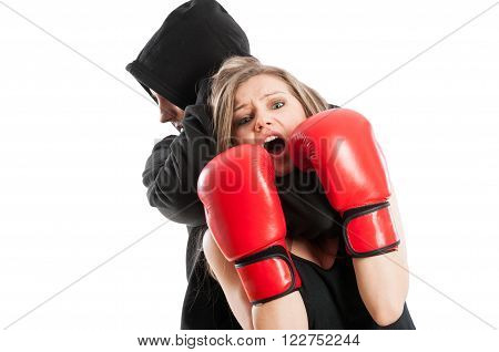 Male aggressor grabbing a frightened woman wearing boxing gloves. Female victim concept on white background