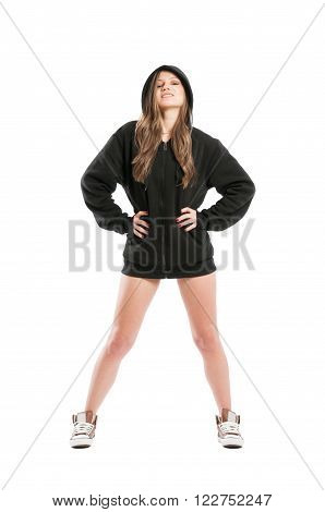 Perky and sexy female wearing a black hoodie standing isolated on white background