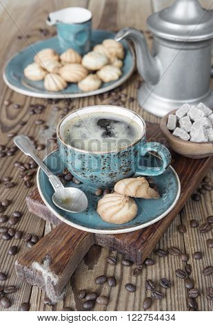 Blue cup of black coffee biscuits creamer coffee pot sugar pieces and coffee beans on old wooden table
