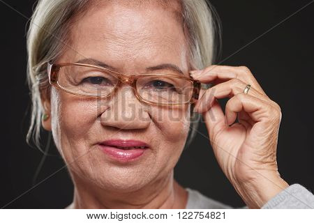 Face of aged Vietnamese woman adjusting her glasses