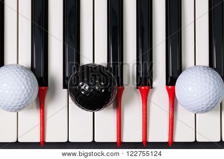 Piano keyboard and different golf balls and wooden tees