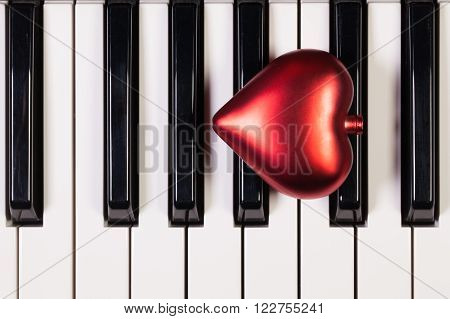 Detail of piano keyboard and red heart