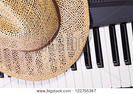 Detail of piano keyboard and straw hat
