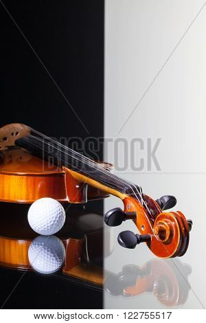 Old violin and golf ball isolated on black and white background and glass desk