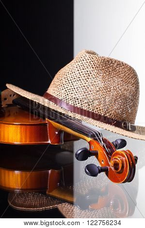 Old violin and straw hat isolated on black and white background and glass desk