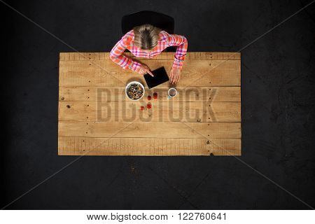 Top view creative photo of girl sitting at wooden vintage table. Girl with plate full of delicious meal. Girl using tablet computer