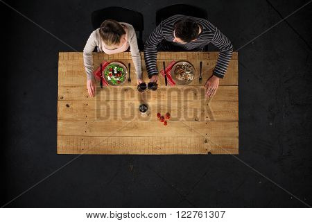 Top view creative photo of couple sitting at wooden vintage table. Man and woman having romantic dinner. They with plates full of delicious meal and glasses with wine