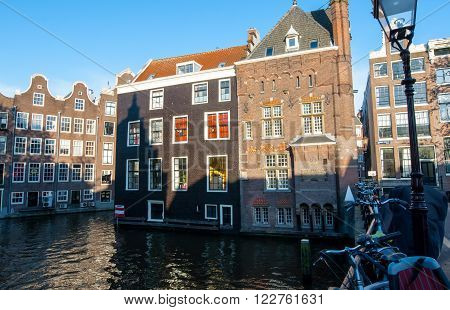 Amsterdam buildings on the water in red light district with bikes on the bridge. The Netherlands.