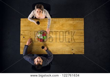 Top view creative photo of couple sitting at wooden vintage table. Man and woman having romantic dinner. They with cheese plate and glasses with wine. Couple looking at camera