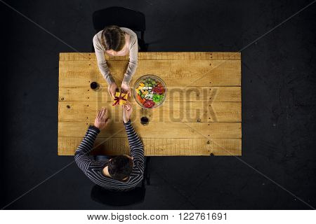 Top view creative photo of couple sitting at wooden vintage table. Man and woman having romantic dinner. They with cheese plate and glasses with wine. Man presenting gift to woman