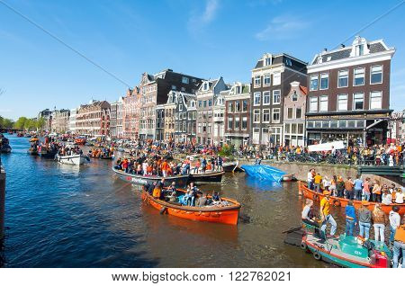 AMSTERDAM-APRIL 27: Local people and tourists on the boats participate in celebrating King's Day through Singel canal on April 272015. King's Day is the largest open-air festivity in Amsterdam.