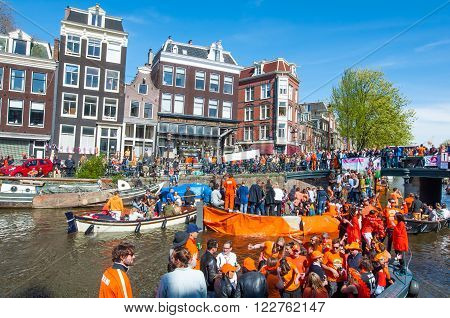 AMSTERDAM-APRIL 27: Crowd of people on the boats participate in celebrating King's Day on April 272015 the Netherlands. King's Day is the largest open-air festivity in Amsterdam.