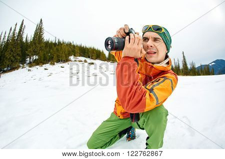 Hiking photographer taking pictures. Treking  in the winter mountains.