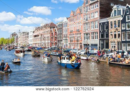 AMSTERDAM-APRIL 27: The celebration of the King's Day along the Singel canal on April 272015 the Netherlands. King's Day is the biggest festival celebrating the birth of Dutch royalty.