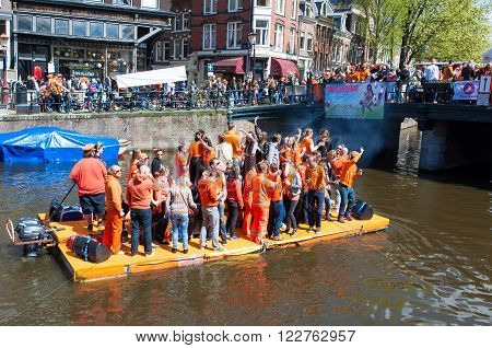 AMSTERDAM-APRIL 27: People celebrate King's Day along the Singel canal on the raft on April 272015 the Netherlands. King's Day is the biggest festival celebrating the birth of Dutch royalty.