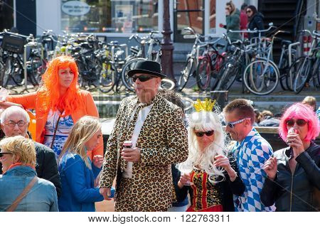 AMSTERDAM-APRIL 27: Unidentified people celebrate King's Day along the Singel canal on April 272015 the Netherlands. King's Day is the largest open-air festivity in Amsterdam.