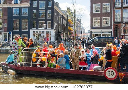 AMSTERDAM-APRIL 27:Unidentified people on the boat celebrate King's Day along the Singel canal on April 272015 the Netherlands. King's Day is the largest open-air festivity in Amsterdam.