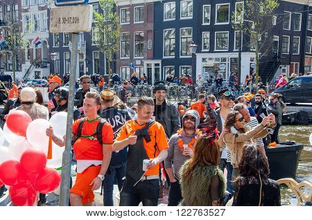 AMSTERDAM-APRIL 27: Locals and tourists in orange have fun on a boat during King's Day the Singel canal on April 272015 the Netherlands.