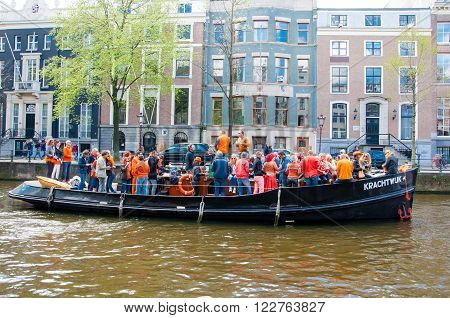 AMSTERDAM-APRIL 27: Crowd of people have dance party on a boat King's Day along the Singel canal on April 272015 the Netherlands. King's Day is the largest open-air festivity in Amsterdam.