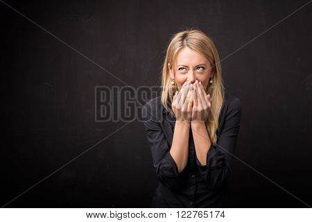 Woman giggles and covers her face with both hands