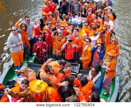 AMSTERDAMNETHERLANDS-APRIL 27: Locals dressed in orange celebrate King's Day on a boat on April 272015 in Amsterdam. King's Day is the largest open-air festivity in Amsterdam.