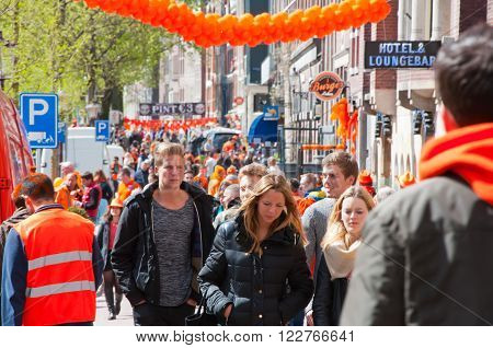 AMSTERDAMNETHERLANDS-APRIL 27: Crowd of people on the street on King's Day on April 2727 in Amsterdam. King's Day is the largest open-air festivity in Amsterdam.