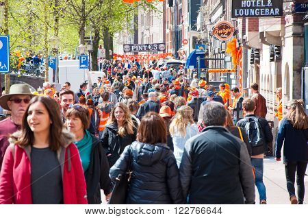AMSTERDAMNETHERLANDS-APRIL 27: Busy street around red light district on King's Day on April 2727 in Amsterdam. King's Day is the largest open-air festivity in Amsterdam.