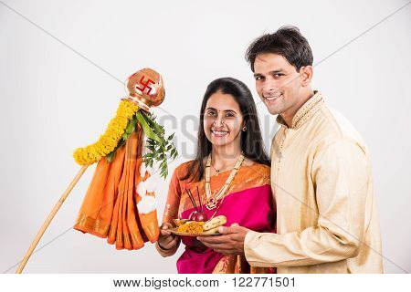 smart indian couple in traditional wear performing gudhi padwa puja, asian couple & puja thali, indian young couple with puja or pooja thali, hindu new year gudhi / gudi padwa, isolated on white