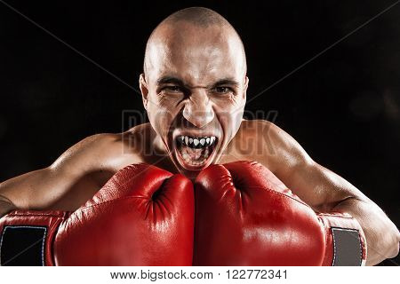 The young male athlete kickboxing on a black background with kapa in mouth. concept fury in the fight