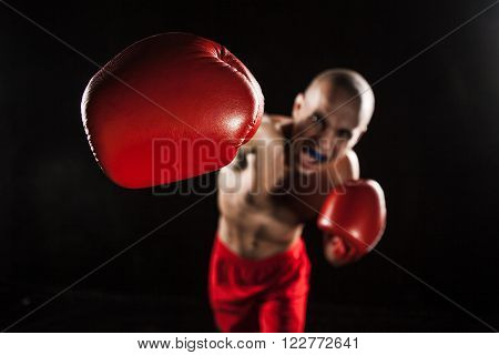 The young male athlete kickboxing on a black background  with kapa in mouth. concept fury in the fight ** Note: Shallow depth of field