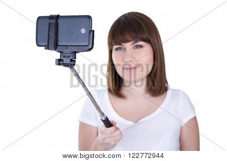 Young Beautiful Woman Taking Photo On Smart Phone With Selfie Stick Isolated On White