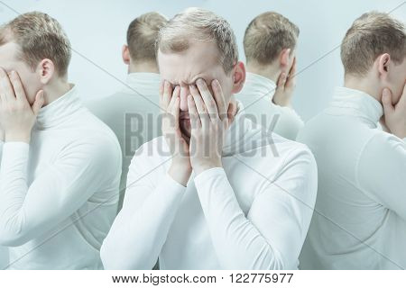 Man with mental problem covering his face with hands duplicated image