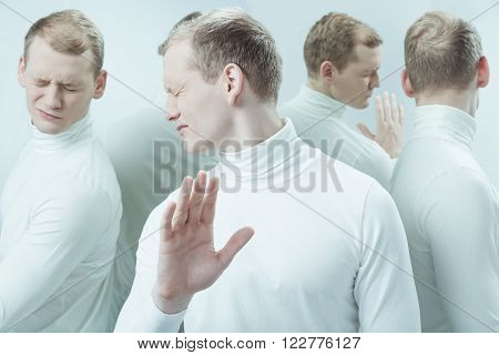 Duplicated image of ill man with grimace on face standing in light interior