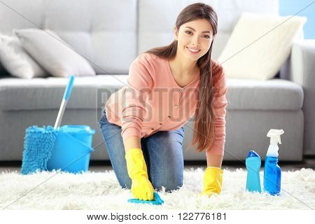 Beautiful woman in protective gloves cleaning carpet with brush and spray