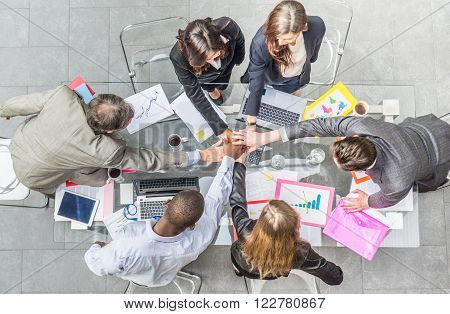 Team of businessmen joining hands during a successful meeting - CEO and managers in a company office concepts about team work and unity view from above