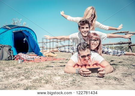 Group of playful friends having fun in a campsite during an open-air concert event - Young cheerful people taking a selfie on a summer holiday in the nature