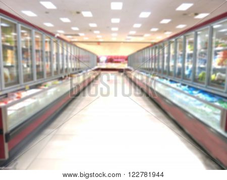 Supermarket corridor with freezers for frozen foods, blurred background
