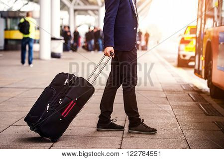 Unrecognizable businessman with luggage waiting at the airport, going to enter a bus, sunny day