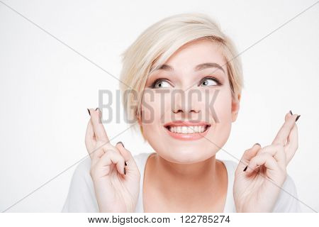 Closeup portrait of a smiling woman with fingers crossed gesture isolated on a white background