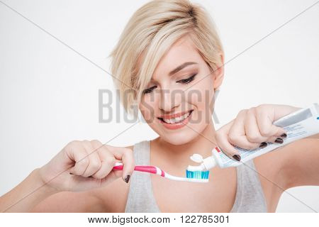 Smiling woman holding a toothbrush and placing toothpaste isolated on aw hite background poster