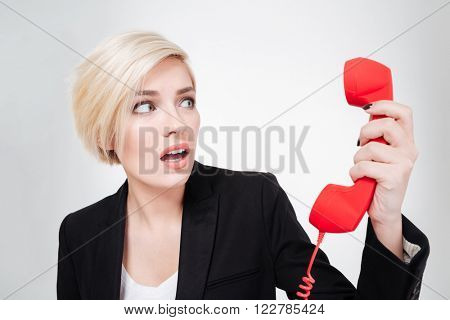 Scared businesswoman holding phone tube isolated on a white background