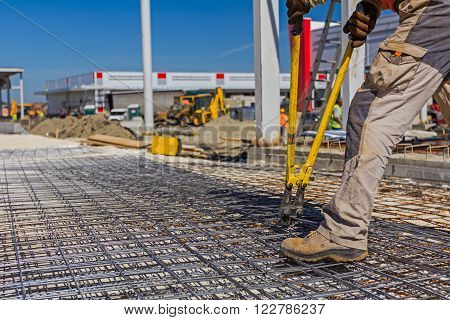Worker is cutting reinforcement mesh with bolt cutters at a building site.