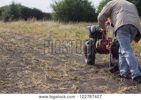 DIKANKA UKRAINE - SEPTEMBER 30 2015: Country farmer is plowing his garden with walk-behind garden tractorautumn field work