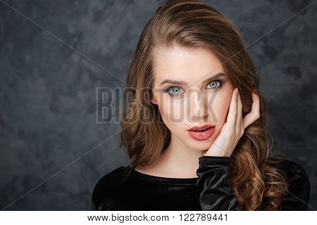Beauty portrait of charming gentle young woman touching sking on her face by hand over grey background