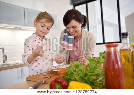 Mom and daughter cooking together in modern kitchen