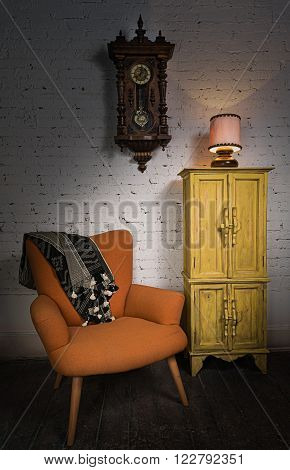 Still life of vintage orange armchair, yellow cupboard, wooden pendulum clock and illuminated table lamp on a wooden floor and white bricks wall