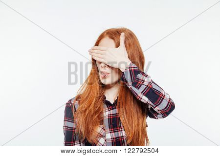 Redhead woman covering her eyes and showing tongue isolated on a white background