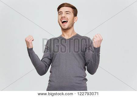 Happy excite young man in grey pullover screaming and celebrating his succcess over white background