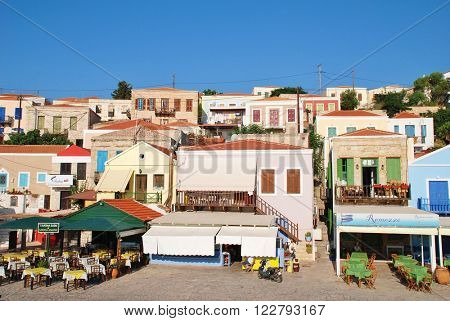 HALKI, GREECE - JUNE 17, 2015: Tavernas and shops on the seafront at Emborio on the Greek island of Halki. The Dodecanese island near Rhodes has a population of under 300 people.